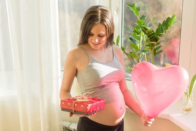 Giovane donna incinta felice con il contenitore di regalo e l'aerostato del cuore Foto Premium