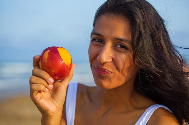 Giovane donna indiana che mangia frutta sulla spiaggia Foto Premium