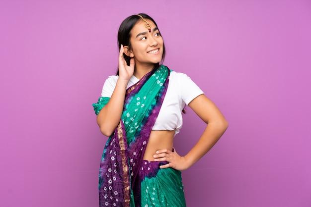 Giovane donna indiana con i sari sopra la parete isolata che pensa un'idea Foto Premium