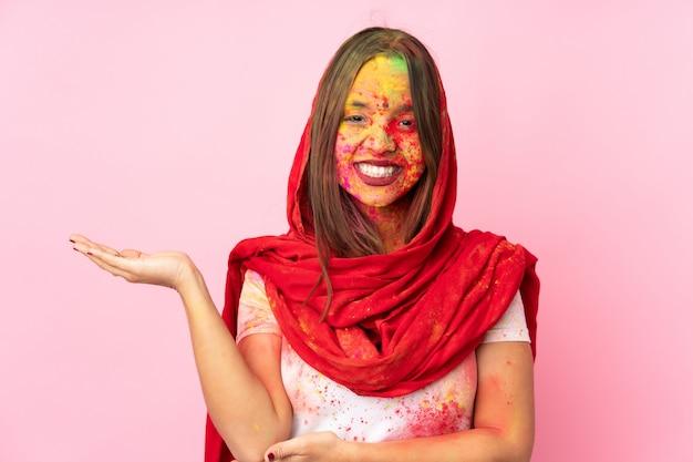 Giovane donna indiana con polveri colorate di holi sul viso sul muro rosa con dubbi Foto Premium