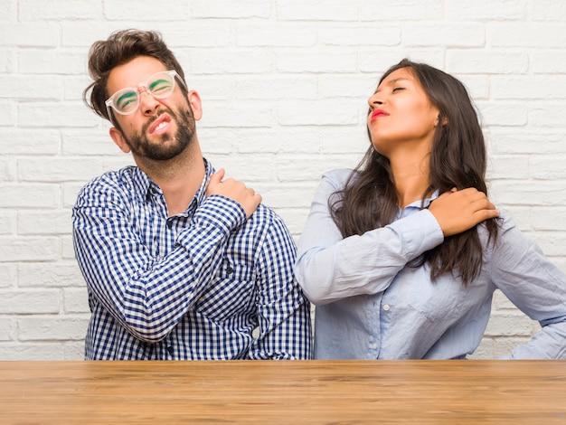 Giovane donna indiana e coppia uomo caucasico con dolore alla schiena a causa di stress da lavoro, stanco e astuto Foto Premium