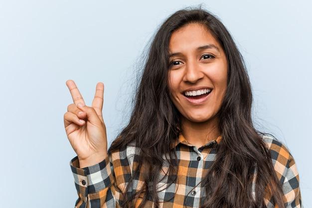 Giovane donna indiana fresca allegra e spensierata mostrando un simbolo di pace con le dita. Foto Premium