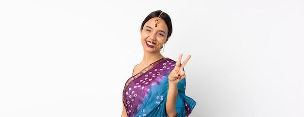 Giovane donna indiana isolata su spazio bianco che sorride e che mostra il segno di vittoria Foto Premium
