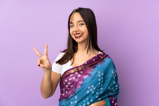 Giovane donna indiana isolata sulla porpora che sorride e che mostra il segno di vittoria Foto Premium