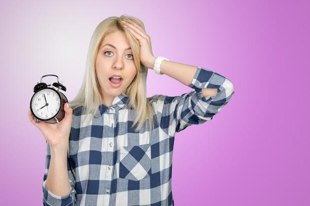 Giovane donna interessata che indica sull'orologio Foto Premium