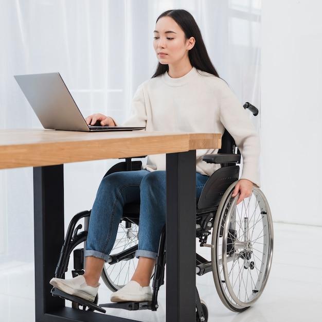 Giovane donna invalida che si siede sulla sedia a rotelle facendo uso del computer portatile Foto Gratuite