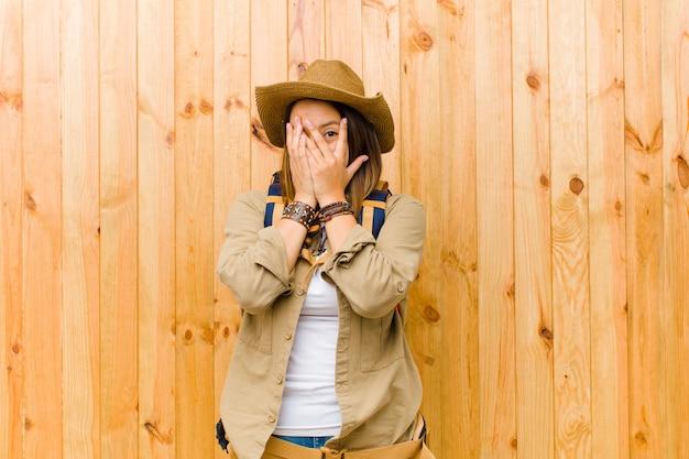 Giovane donna latina dell'esploratore contro il fondo di legno della parete Foto Premium