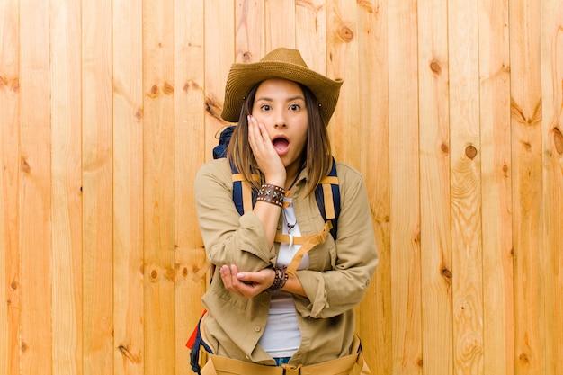 Giovane donna latina dell'esploratore contro la parete di legno Foto Premium