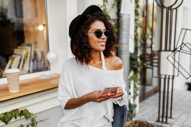 Giovane donna mista con acconciatura afro parlando al telefono cellulare e sorridente in urbano Foto Gratuite