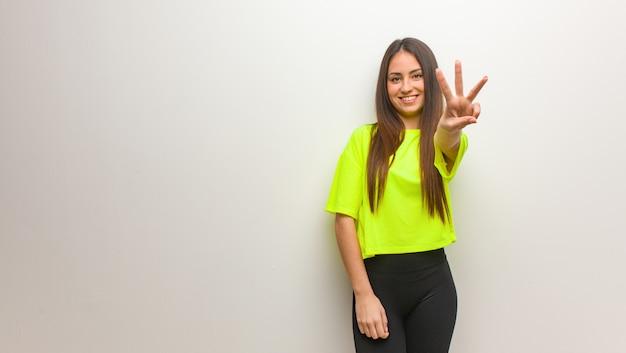 Giovane donna moderna che mostra numero tre Foto Premium