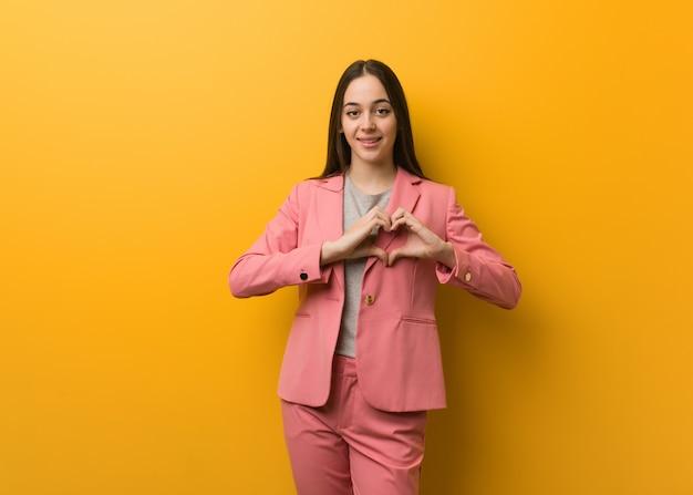Giovane donna moderna di affari che fa una forma del cuore con le mani Foto Premium