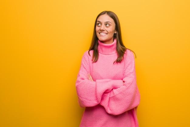 Giovane donna moderna sorridente fiducioso e attraversando le braccia, alzando lo sguardo Foto Premium