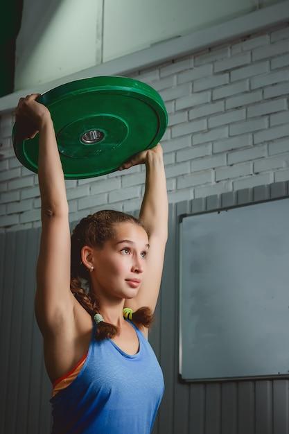 Giovane donna muscolare di forma fisica che solleva un crossfit del peso nella palestra. crossfit Foto Premium