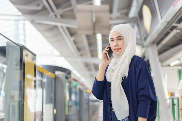 Giovane donna musulmana che per mezzo del telefono sulla stazione dello skytrain. Foto Premium