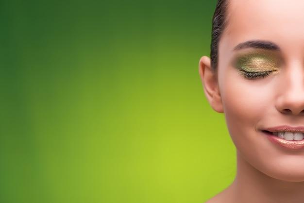 Giovane donna nel concetto di bellezza su verde Foto Premium