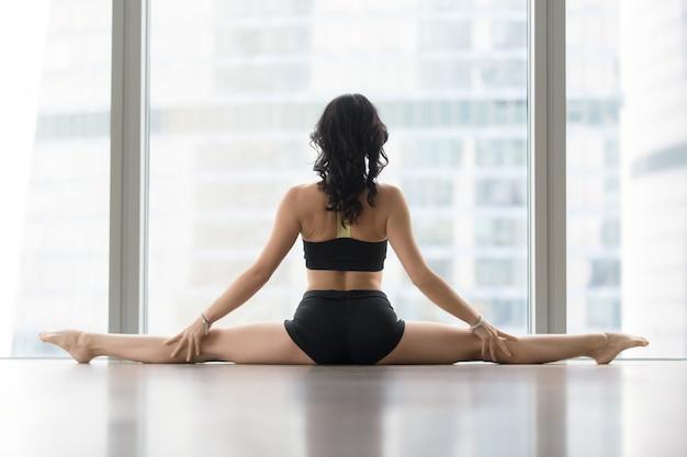 Giovane donna nella posa di samakonasana contro la finestra del pavimento, retrovisione Foto Gratuite