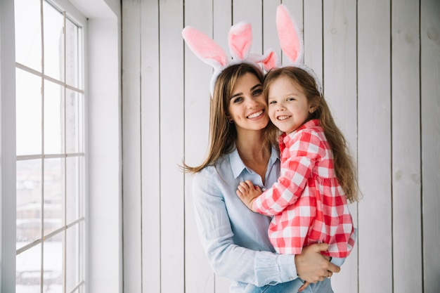 Giovane donna nelle orecchie del coniglietto che tiene figlia in armi Foto Gratuite