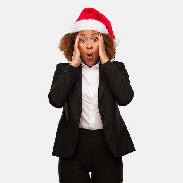 Giovane donna nera di affari che indossa un cappello di santa di chirstmas sorpreso e colpito Foto Premium