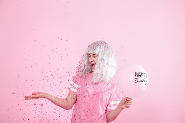 Giovane donna o ragazza con palloncini buon compleanno. lancia coriandoli dall'alto. concetto di festa e festa. Foto Gratuite