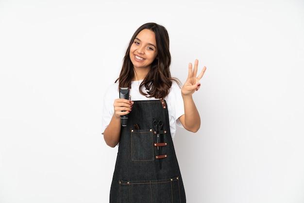 Giovane donna parrucchiere sul muro bianco felice e contando tre con le dita Foto Premium