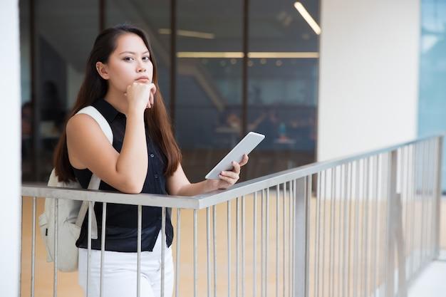 Giovane donna pensierosa con il pc della compressa che esamina macchina fotografica Foto Gratuite