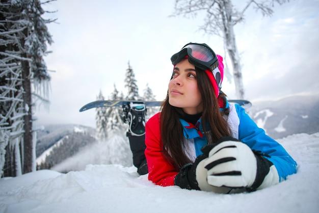 Giovane donna pensierosa in inverno nella foresta nevosa in cima alle montagne Foto Premium