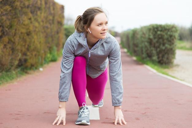 Giovane donna pensierosa nella posizione di partenza pronta per correre Foto Gratuite