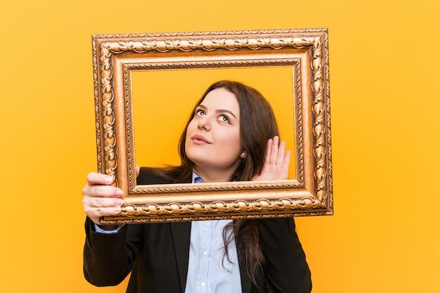 Giovane donna più curvy di affari di dimensione che tiene una struttura che prova ad ascoltare un gossip. Foto Premium