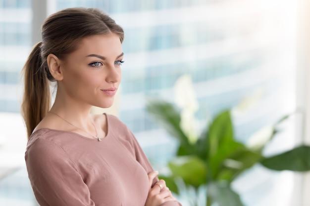 Giovane donna premurosa pensierosa che guarda attraverso la finestra, armi attraversate, all'interno Foto Gratuite