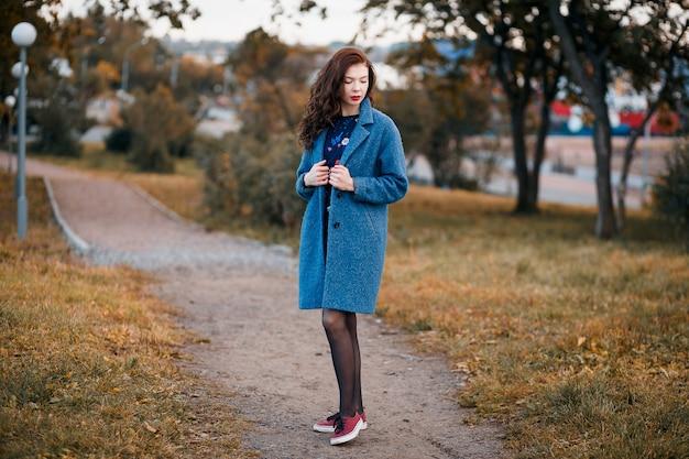 Giovane donna riccia alla moda in autunno nel parco che indossa cappotto blu e scarpe da tennis rosse Foto Premium