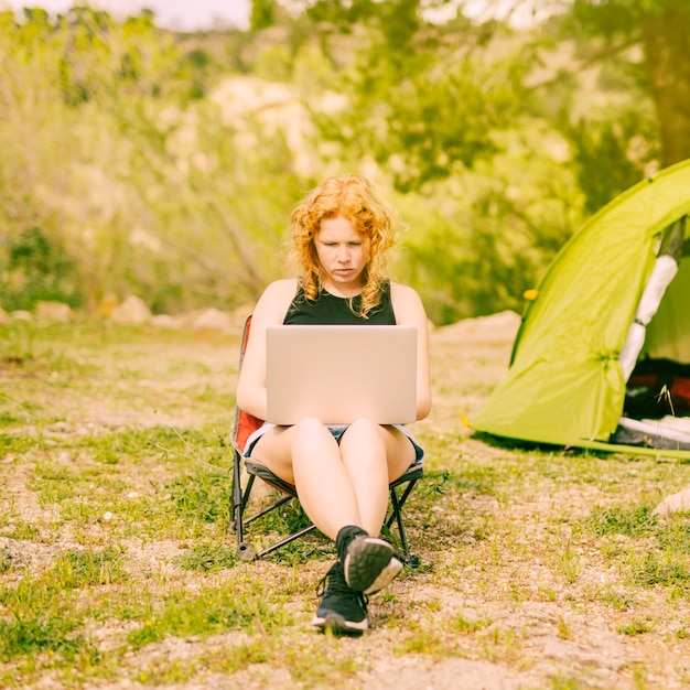 Giovane donna riccia che pratica il surfing sul computer portatile sulla natura Foto Gratuite