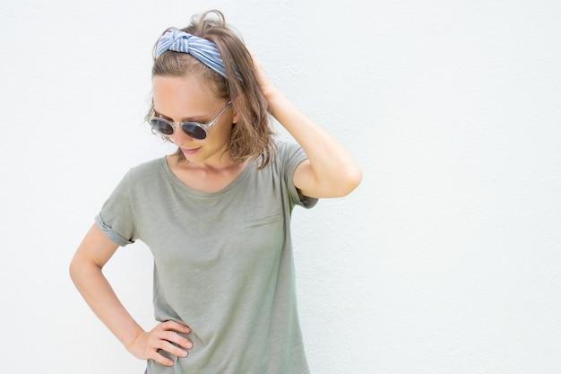 Giovane donna rilassata che indossa abiti estivi e occhiali da sole Foto Gratuite