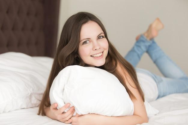 Giovane donna rilassata che si trova a letto sullo stomaco Foto Gratuite