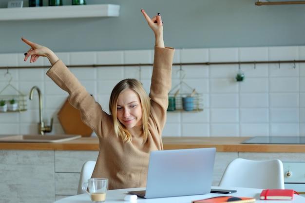 Giovane donna rilassata felice che si siede nella sua cucina con un computer portatile Foto Premium