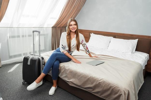 Giovane donna sdraiata nel letto di una camera d'albergo Foto Premium