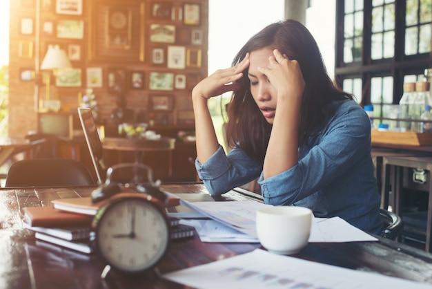Giovane donna seduta in un caffè con il suo portatile, stressante per wor Foto Gratuite