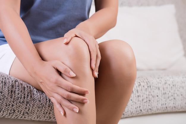 Giovane donna seduta sul divano e sensazione di dolore al ginocchio. Foto Premium