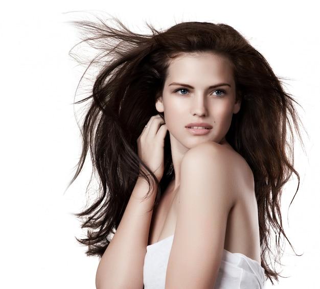 Giovane donna sensuale con bei capelli marroni lunghi di volo, posante i Foto Premium