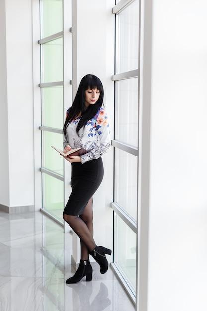 Giovane donna seria attraente che sta vicino alla finestra in un ufficio, tenente un taccuino, guardante fuori alla finestra. Foto Premium