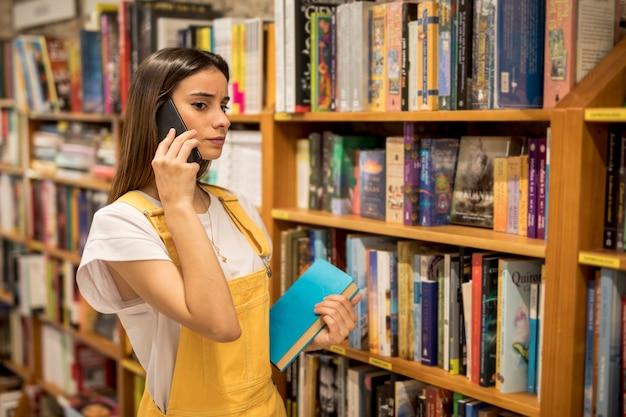 Giovane donna seria che parla sul telefono vicino agli scaffali per libri Foto Gratuite