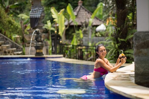 Giovane donna sexy in costume da bagno rosa con la bevanda di cocco in piscina in vacanza. Foto Premium
