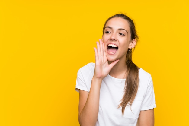 Giovane donna sopra fondo giallo isolato che grida con la bocca spalancata Foto Premium
