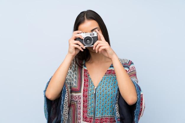 Giovane donna sopra la parete blu isolata che tiene una macchina fotografica Foto Premium