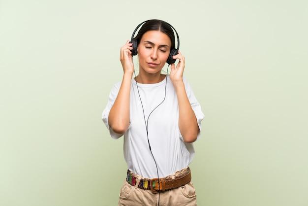 Giovane donna sopra la parete verde isolata che ascolta la musica con le cuffie Foto Premium