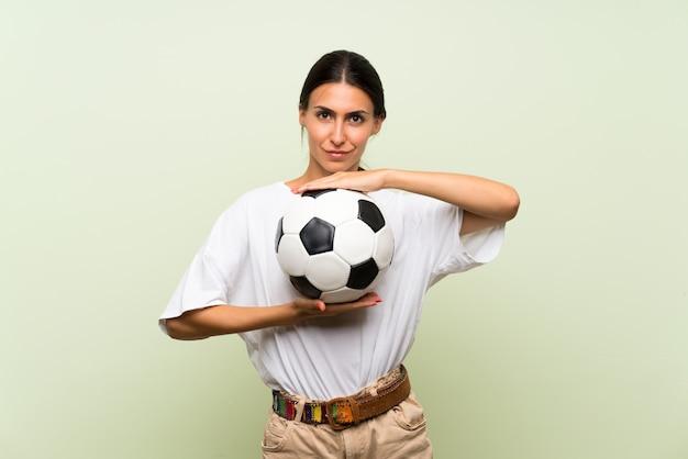 Giovane donna sopra la parete verde isolata che tiene un pallone da calcio Foto Premium