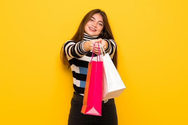 Giovane donna sopra sulla parete gialla che tiene molti sacchetti della spesa Foto Premium