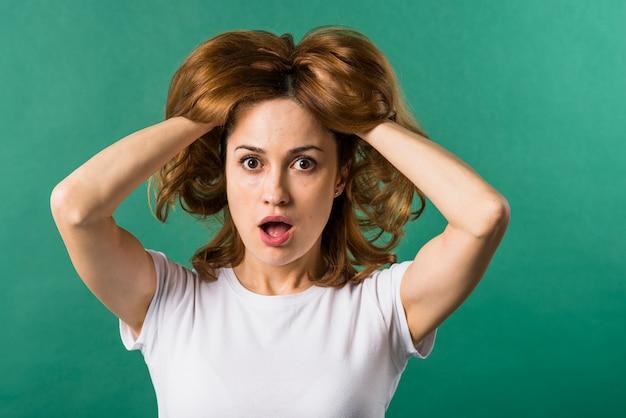 Giovane donna sorpresa con le sue due mani nei capelli contro il contesto verde Foto Gratuite