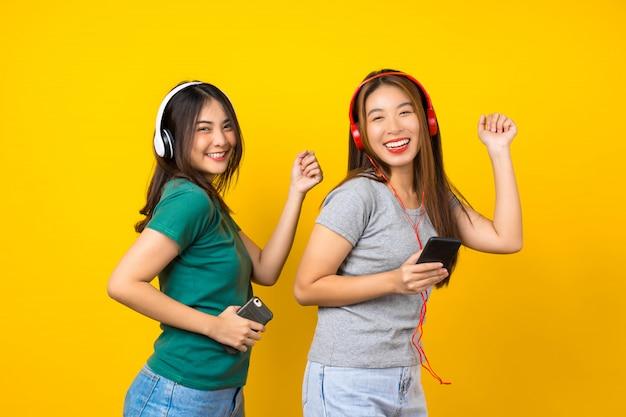 Giovane donna sorridente asiatica di due felicità che indossa le cuffie senza fili per ascoltare musica tramite telefono cellulare astuto e ballare sulla parete gialla isolata, stile di vita e svago con il concetto di hobby Foto Premium