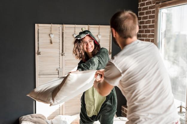 Giovane donna sorridente che fa lotta di cuscino con il suo marito a casa Foto Gratuite