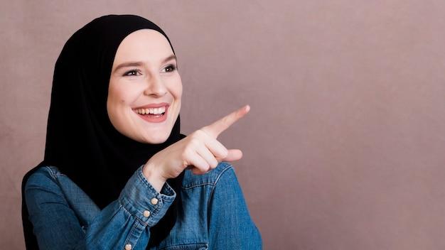 Giovane donna sorridente che indica a qualcosa sopra fondo normale Foto Gratuite
